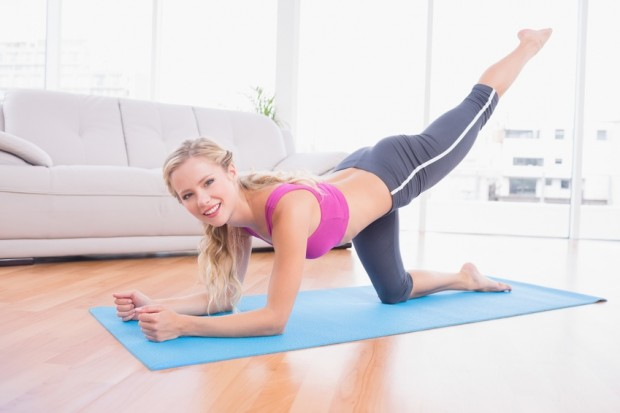 Toned blonde doing pilates on exercise mat smiling at camera